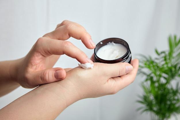 Woman applying moisturizer to her skin of hand Premium Photo