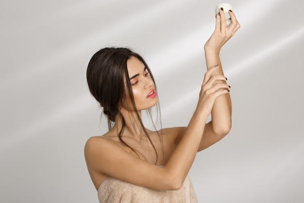 Woman applying moisturizer on left hand after bathing. beauty care. Free Photo