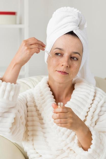 Женщина наносит увлажняющий крем на лицо Бесплатные Фотографии