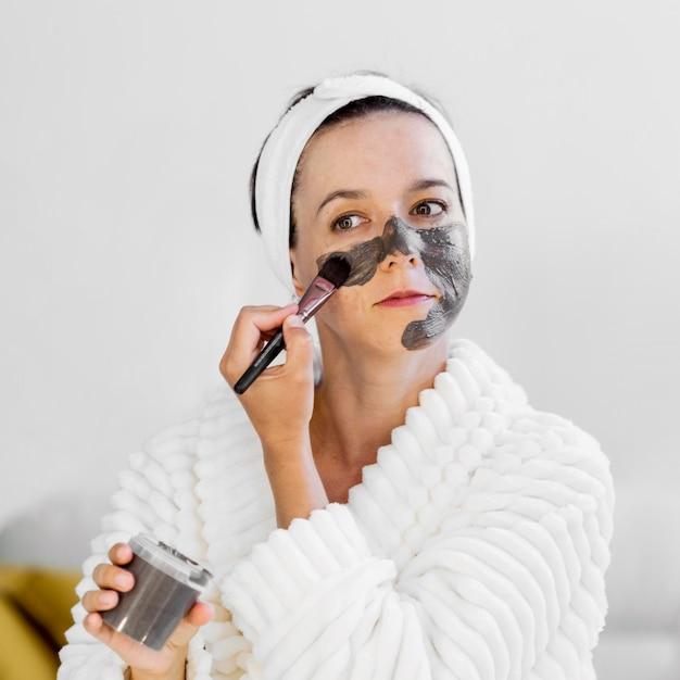 Женщина, применяющая спа-органическую маску для лица с кистью Бесплатные Фотографии