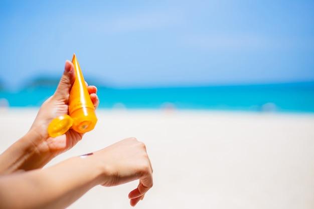 Woman applying sunscreen protection cream against turquoise caribbean sea Premium Photo