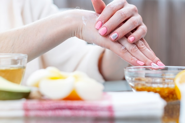 Женщина, применяя крем на руках, питая их натуральной косметикой крупным планом. гигиена и уход за кожей Premium Фотографии