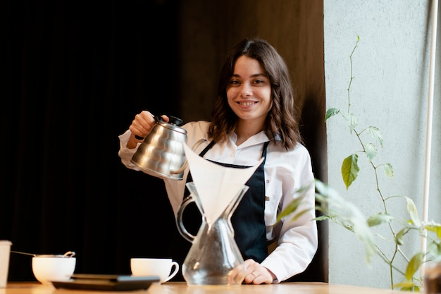 Woman in apron posing with coffee pot Free Photo
