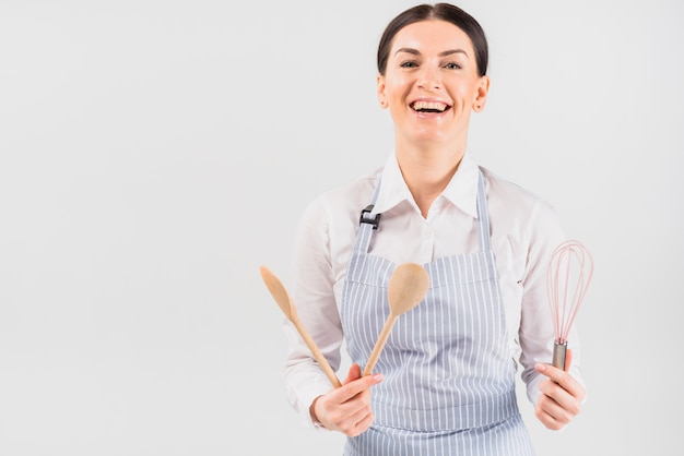 Woman in apron smiling and holding utensil Free Photo