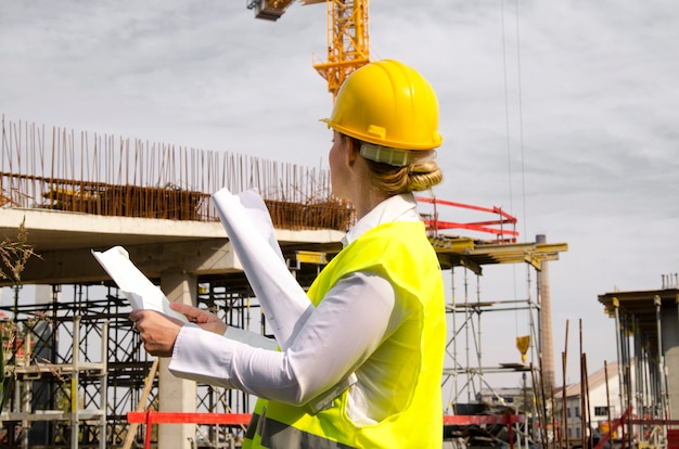 Woman architect at construction site with plans in hands looking at new building Premium Photo