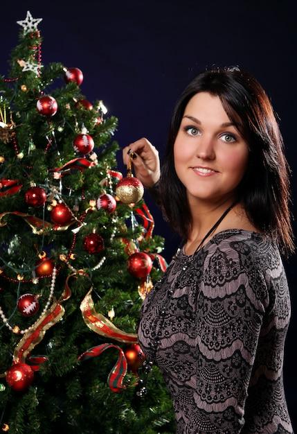 女性はクリスマスツリーを飾っています 無料写真