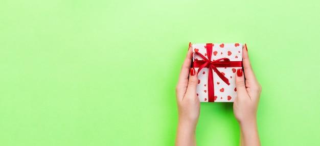 Woman arms holding gift box Premium Photo