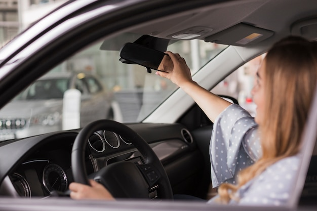 Woman arranging rear-view mirror Free Photo