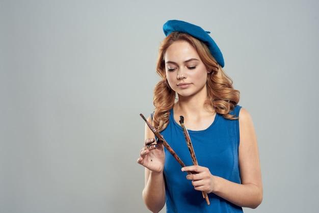 Женщина художник кисть в руке синий берет изолированные Premium Фотографии