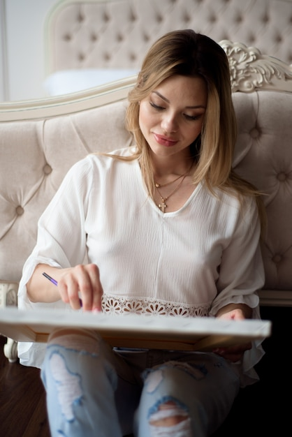 Woman artist drawing her picture on canvas with oil colors at home Premium Photo
