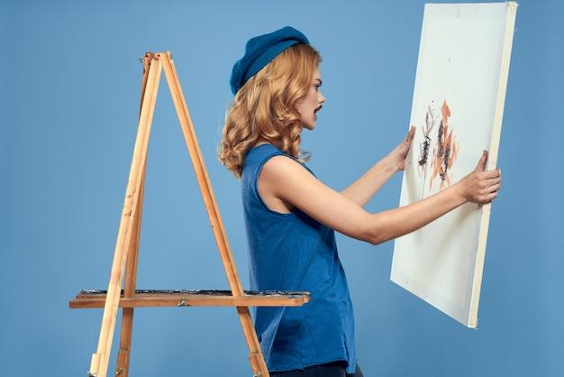 Художник женщина держит картину в руках Premium Фотографии