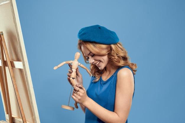 Художник женщины держа деревянное искусство мольберта манекена в руках предпосылка творческого хобби голубая. Premium Фотографии