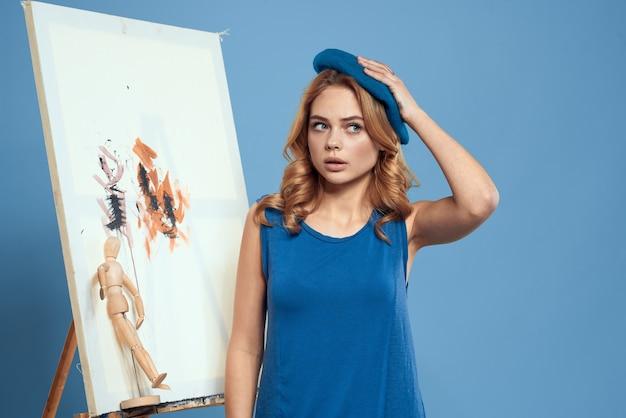 Краска кисти художника женщины на предпосылке голубого образования искусства мольберта холста. Premium Фотографии