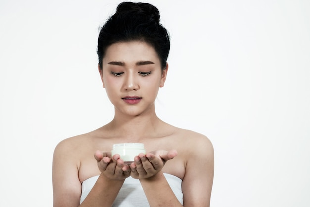 Woman asian using a skin care product a white background.girl is happy with the skin crea Premium Photo