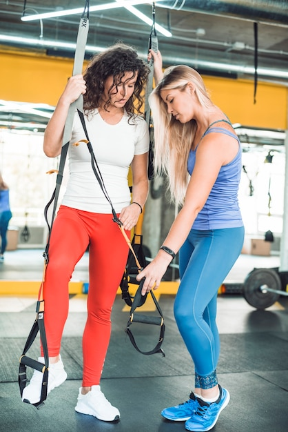 Woman assisting her friend while exercising with fitness strap in gym Free Photo