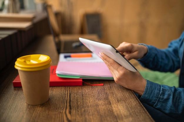 Женщина в кафе ждет своих друзей, чтобы сделать домашнее задание Premium Фотографии