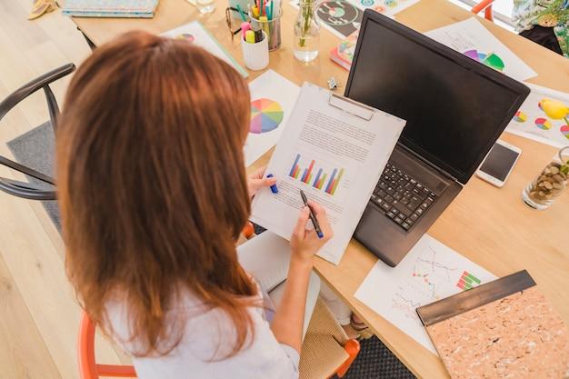 Woman at desktop exploring diagrams Free Photo