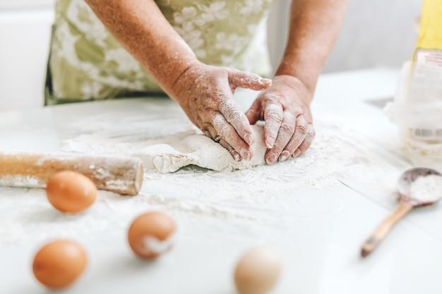 パスタピザやパンを調理するための生地を練る自宅の女性。家庭料理のコンセプトです。暮らし 無料写真