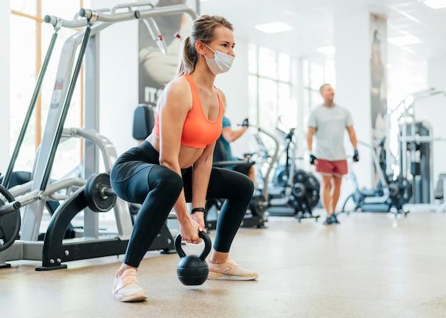 Женщина в тренажерном зале тренируется с маской Premium Фотографии