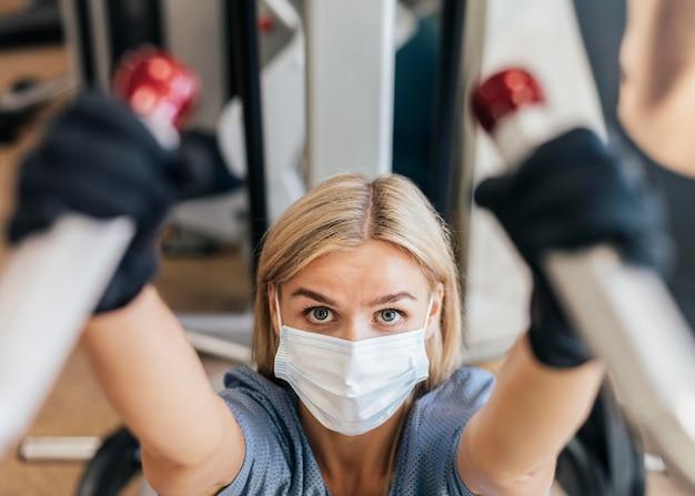 Женщина в тренажерном зале с использованием оборудования с маской на Бесплатные Фотографии