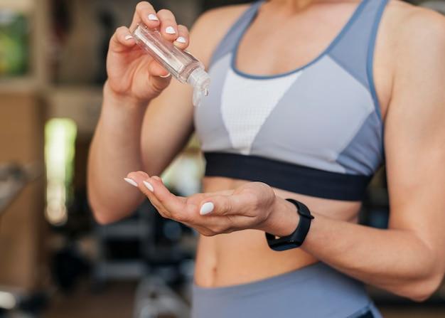 Женщина в тренажерном зале, используя дезинфицирующее средство для рук Бесплатные Фотографии