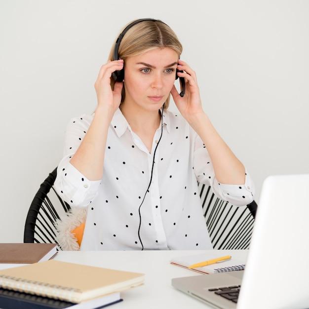 ヘッドフォンを使用してオンラインコースに参加する女性 無料写真