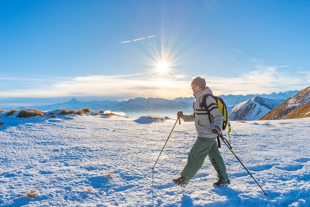 Woman backpacker trekking on snow on the alps. Premium Photo