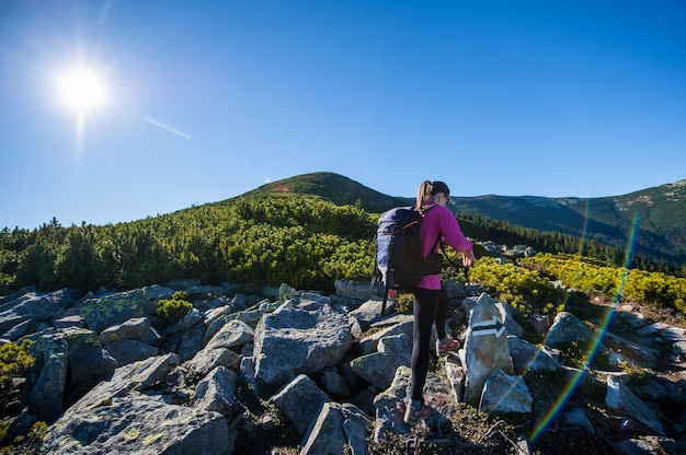 Woman backpacker walking on the rocky trail Premium Photo