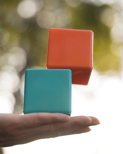Donna che equilibra i cubi di plastica colorati Foto Gratuite