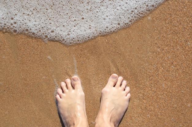 Женщина босиком на песке с морской пеной Premium Фотографии