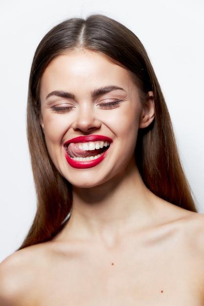 Женщина с открытыми плечами и закрытыми глазами показывает язык естественный свет Premium Фотографии