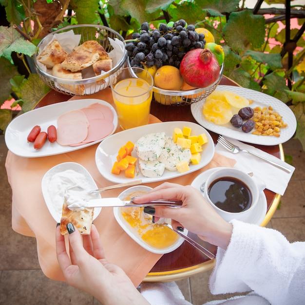 Donna in un accappatoio che mangia prima colazione fuori nella vista laterale di mattina Foto Gratuite