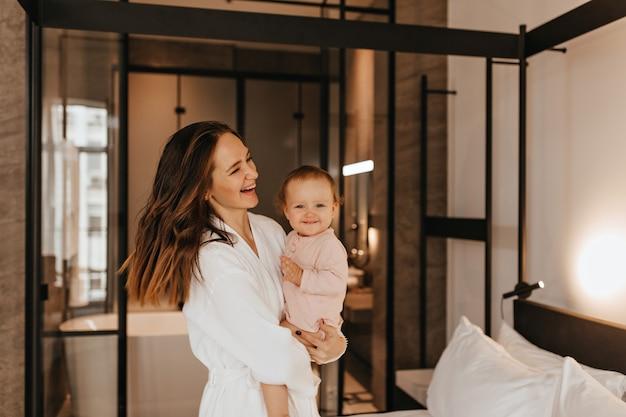 La donna in accappatoio tiene un bambino piccolo e sorridente. ritratto di madre con figlia in camera da letto. Foto Gratuite