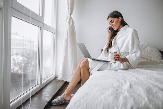 Woman in bathrobe sitting in bed Free Photo