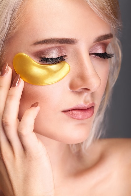 Woman beauty face with mask under eyes. beautiful female with natural makeup and gold collagen patches. Premium Photo