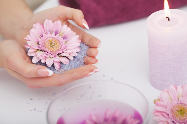 Woman in beauty salon holding fingers in aroma bath for hands. Premium Photo