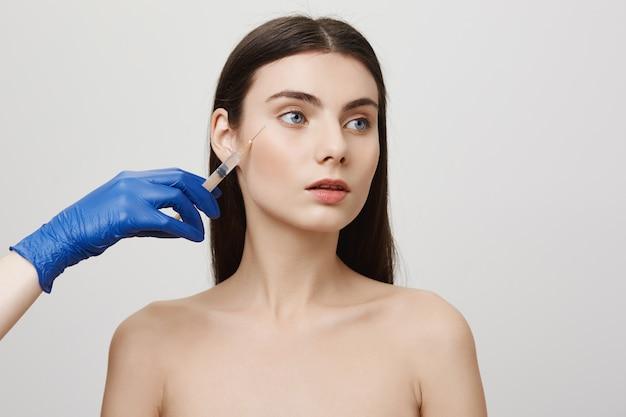 La donna nel salone di bellezza distoglie lo sguardo, riceve l'iniezione del viso di bottox con la siringa Foto Gratuite