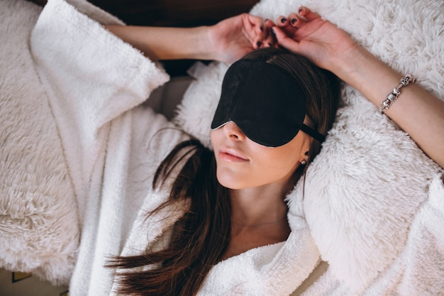 Woman in bed wearing sleeping mask Free Photo