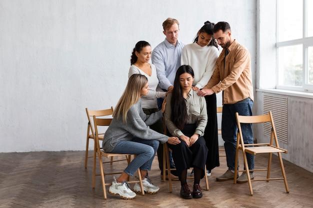 Donna consolata da persone in una sessione di terapia di gruppo Foto Gratuite