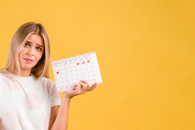 Woman being upset and holding the period calendar Free Photo