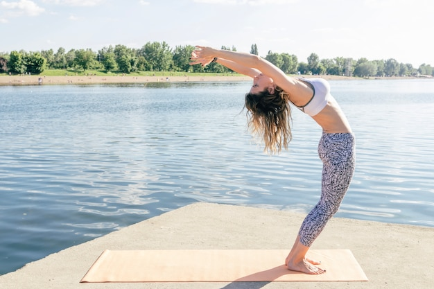 Woman bending back at water Free Photo