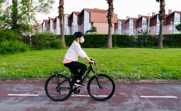 A woman on a bicycle with safety mask on her face | Premium Photo