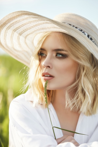 Woman in a big hat and a long white dress is sitting in the grass in a field. blonde woman in the sun in a light dress. woman resting and dreaming, perfect summer makeup on her face Premium Photo