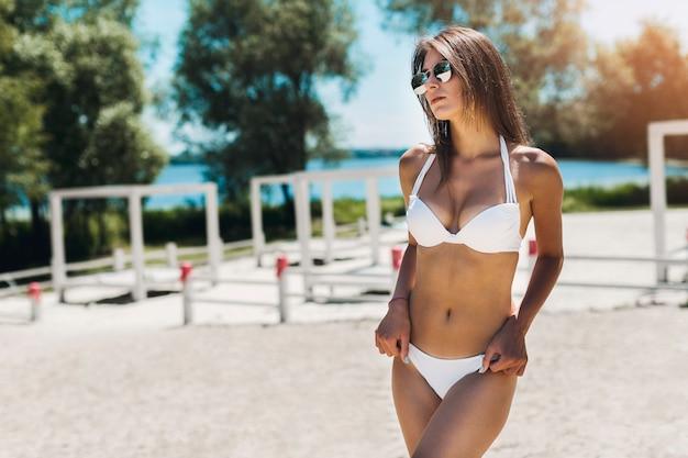 Woman in bikini keeping hands on hips Free Photo