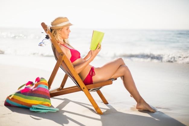 Woman in bikini sitting on armchair and reading book Premium Photo