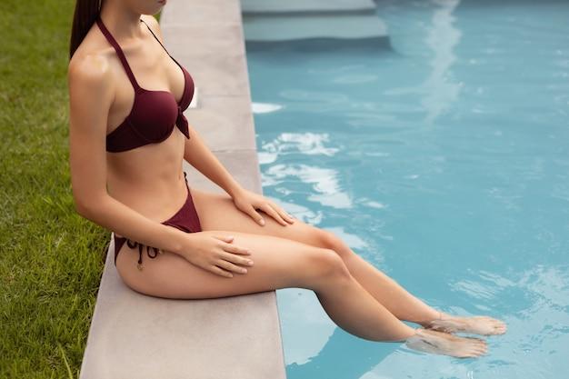 Woman in bikini sitting on the edge of swimming pool Free Photo