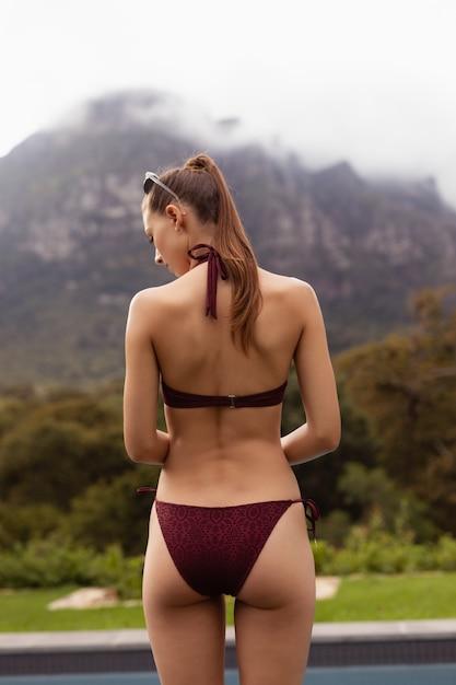 Woman in bikini standing near poolside in the backyard Free Photo