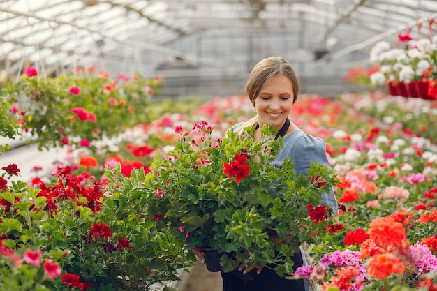 Woman in a black apron working in a greenhouse Free Photo