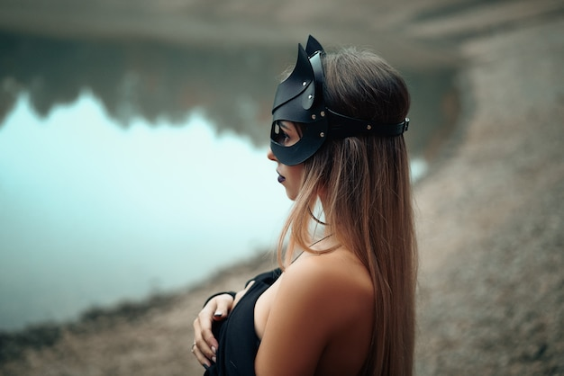 A woman in a black cat mask stands on the background of nature. Premium Photo
