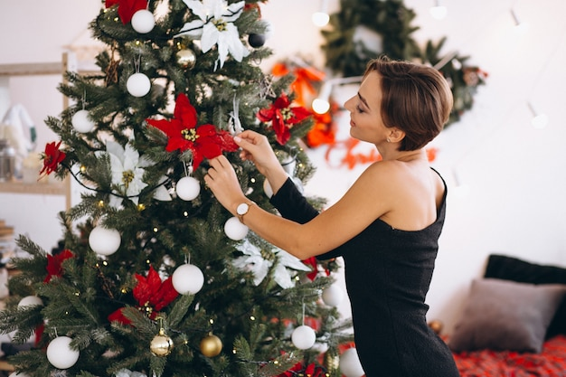 Woman in black dress by christmas tree Free Photo